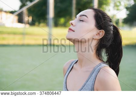 Side View Of Young Beautiful Female With Closed Eyes Breathing Deeply While Doing Respiration Exerci