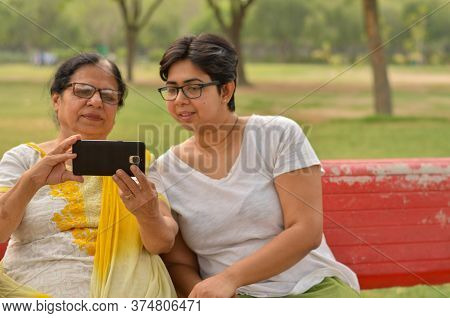 Young Indian Girl With Her Old Indian Mother Looking At The Mobile Phone And Busy Talking Selfie On