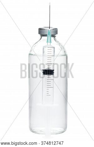 Syringe With A Needle Filled With A Dose Of Vaccine In The Background Glass Bottle With Medical Prep
