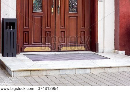Entrance To The Building With A Wooden Door And A Marble Threshold With A Step, Iron Urn At The Faca