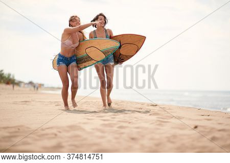Young sexy female surfers enchanted by the sea and the beach