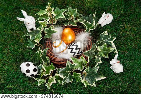 Happy Easter. Gold And Black Painted Eggs In Ivy Nest With Bunnies On A Background Of Moss. Congratu