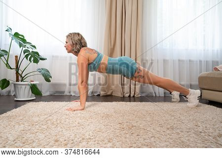 Girl With Tattoos Plays Sports At Home, Exercise Plank Handstand. Online Fitness. Recovery After Chi
