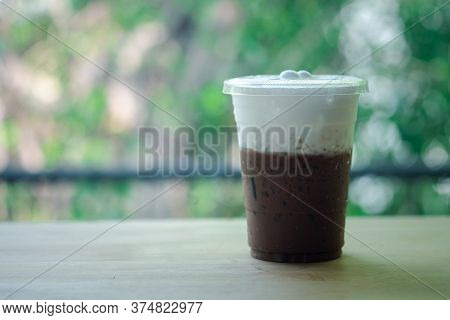 Iced Mocha Coffee In Takeaway Glass And Milk Foam With Nature Background. Show Layer Milk Foam And C