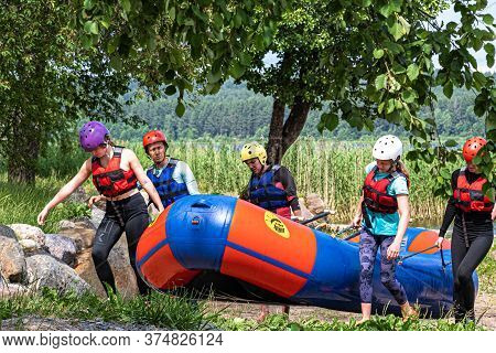 Female Athletes Carry An Inflatable Raft Out Of The Water. Passed The Rapids On The River. Rafting I