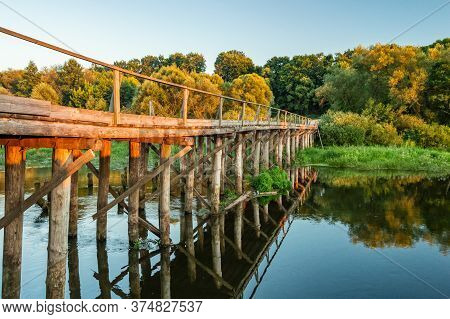 A Small Bridge Over The River In The Forest Against The Background Of The Sunset. Landscape Photo Of