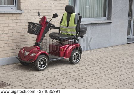 A Red Four Wheel Scooter With A Yellow Fluor Vest Parked Against The Facade Of A House