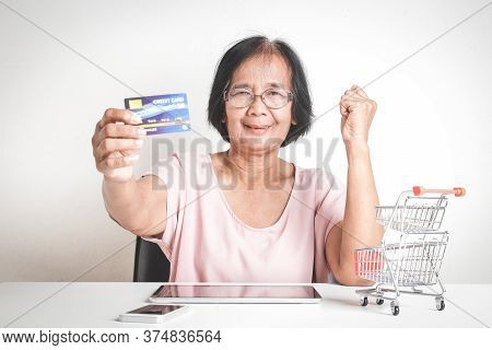 An Elderly Asian Woman Holding A Simulated Credit Card Is Not The Real Thing. Shopping Online. Senio