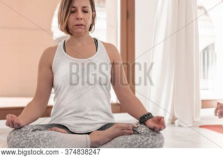 Yoga Teacher Sitting In The Lotus Position. Woman Practicing Yoga. How To Keep Your Arms  For A Kriy