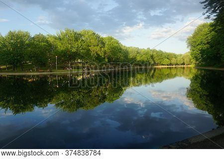 Montreal, Qc / Canada - 7/3/2020: Reflections Of Trees On Lake Water, La Fontaine Park.