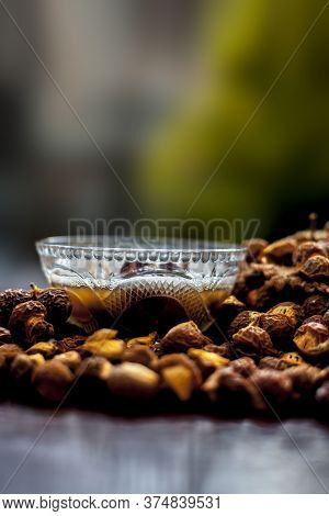 Close Up Shot Of Raw Soapnut And Its Solution In A Glass Bowl On Brown Wooden Surface Shot With Blur