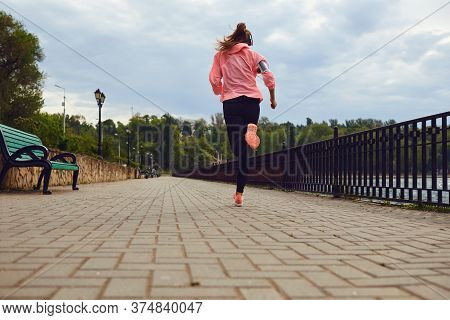 Back View Of Woman In Sportswear Running Along Riverside, Copy Space. Jogger On Training, Getting Re