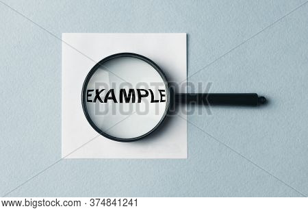 Example Word Inscription On Paper Note Through Magnifier. Example Concept. Searching For Example, Ex