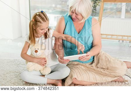 Cute little girl teaching granny to use tablet sitting on floor in light room