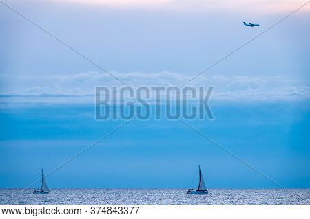 Two Sailing Yachts In The Blue Calm Sea And Landing Plane In The Sky. Yachts In Peaceful Waters And