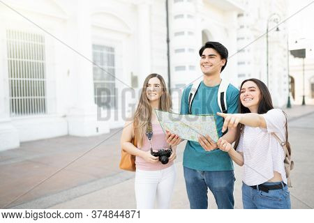 Smiling Young Woman Pointing And Guiding Friends During Trip In City