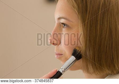 Beautiful, Pretty Young Girl Uses Make-up Brush On Her Face. Closeup.