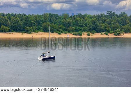 Sailing Boat With A Bare Mast Swinging On The River Waves In The Rain Against The Background Of The