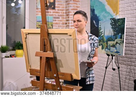 The Artist Works In Her Creative Space, Surrounded By Paintings. Girl Paints A Picture With Oil Pain