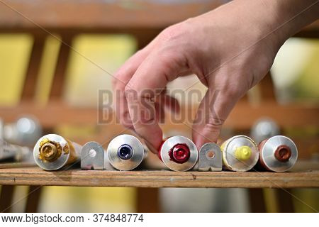 Open Tubes With Oil Paints Are On The Ready, The Hand Takes One Of The Tubes For Color Matching.