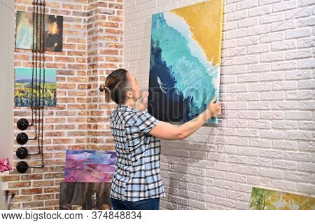 A Girl Hangs A Picture On The Wall In Her Creative Studio, Then Moves Away And Admires The Creation.