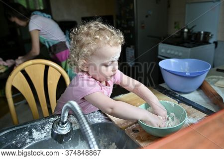 A Little Girl Is Rowdy In The Kitchen While Mom Is Busy Cooking Dinner. Child Plays With Flour In Th