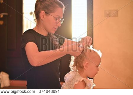 A Close-up Of A Mother Who Plaits Braids For Her Little Daughter. Mom And Baby Spend Time In The Eve