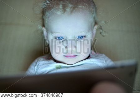 The Little Girl Is Fascinated By The Screen Of The Tablet. The Child Is Watching Cartoons, Front Vie