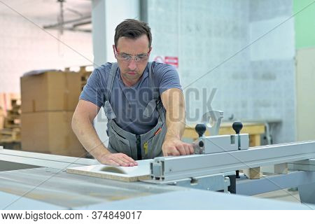 A Young Man Works On A Circular Saw In A Furniture Workshop