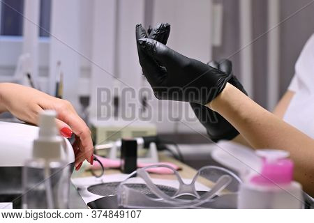 The Master In The Beauty Salon Puts On Black Protective Gloves Before Carrying Out The Client S Skin