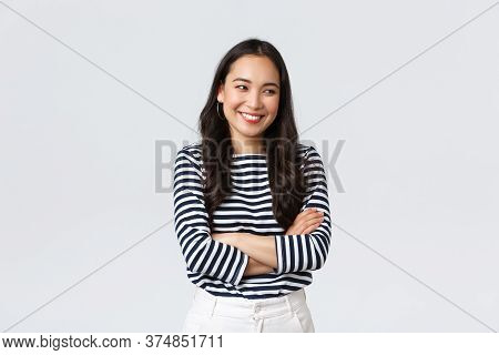Lifestyle, Beauty And Fashion, People Emotions Concept. Cheerful Cute And Shy Asian Girl Cross Arms