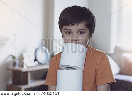 Child Carrying A Stack Of Toilet Paper With Blurry Living Room Background, Kid Holding Toilet Roll,