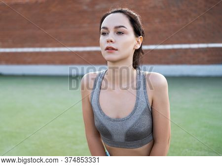 Young Woman Rests After Jogging Against A Red Brick Wall. Caucasian Female Fitness Model Working Out