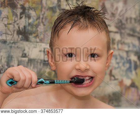 Happy Sympathetic Boy Brushes His Teeth In The Bathroom
