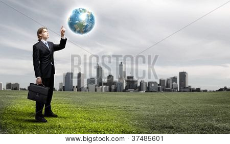 Businessman holding the world in the palm of his hand.Elements of this image furnished by NASA.