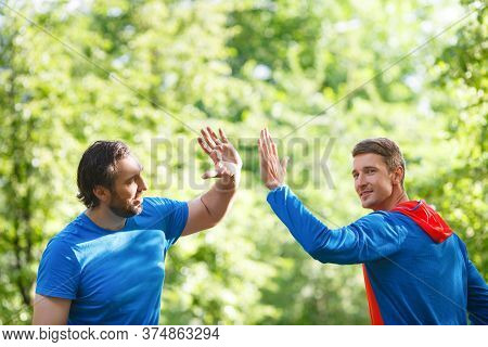 Two Men After Workout Outdoor Giving High Five. Active And Healthy Lifestyle Concept.