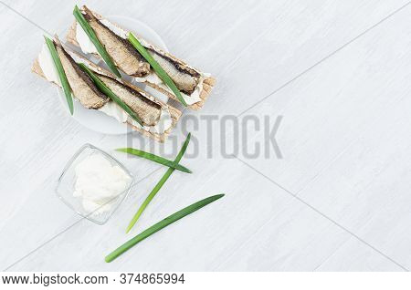 Healthy Dietary Breakfast Of Whole Grain Wheat Crisps Breads With Anchovies, Cream Cheese, Green Oni