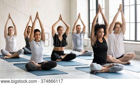 Peaceful Young Multiracial People Sitting In Padmasana Pose.