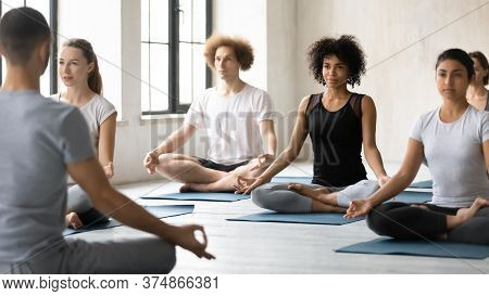 Focused Peaceful Young Mixed Race People Learning Meditating Indoors.