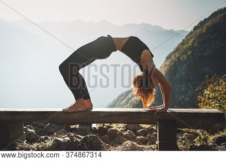 Female Practicing Yoga On Nature. Young Woman Doing Yoga In Mountains. Girl With Slim, Strength And
