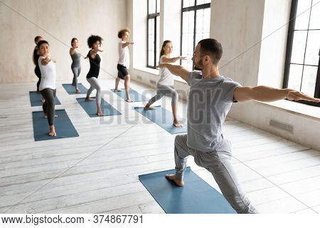Professional Male Fit Trainer Giving Yoga Master Class.
