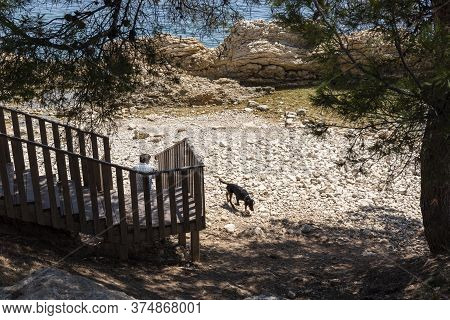 Calvià, Mallorca, Spain - June 03 2020: Man Walking His Dog Through A Cove In Calvià Under The Shade