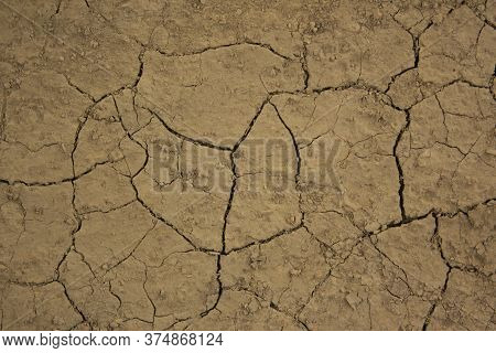 Dry And Cracked Earth. Dried Yellow Soil Crack. Environmental Problem Drought And Thirst. The Textur
