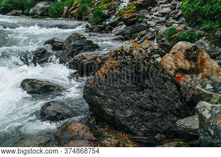 Wonderful Scenic Landscape With Big Mossy Stone Near Mountain River. Green Moss And Orange Lichen On