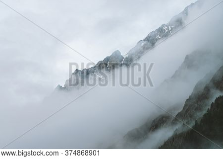 Ghostly Atmospheric View To Big Cliff In Cloudy Sky. Low Clouds Among Giant Rocky Mountains. Mysteri