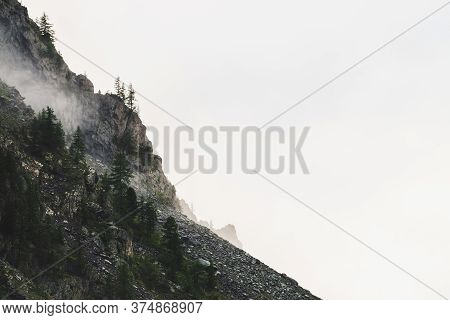 Ghostly Atmospheric View To Big Cliff With Trees In Cloudy Sky. Low Clouds And Giant Rocky Mountains