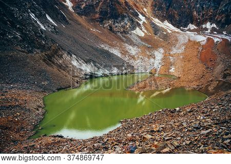 Wonderful Emerald Mountain Lake With Glacier In Mountain Circle Among Rocks And Stones. Most Beautif