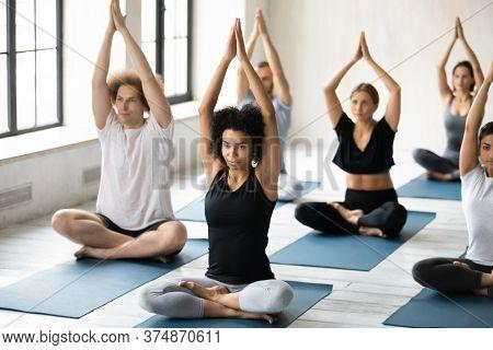 Multiracial Beginners Finishing Pilates Workout In Padmasana Pose.