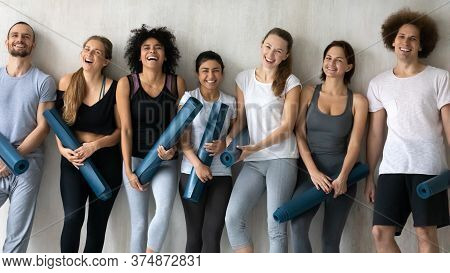 Overjoyed Young Fit Healthy Mixed Race People Holding Rubber Mats.