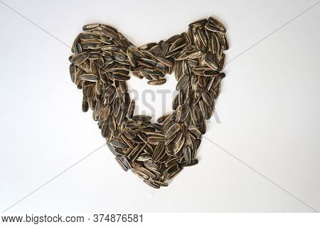 Pile Of Fried Sunflower Seeds With Heart Or Love Shape Isolated On White Background.